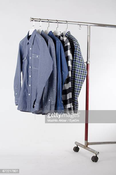 shirts hanging on metallic rack against white background - indonesian cloth 個照片及圖片檔