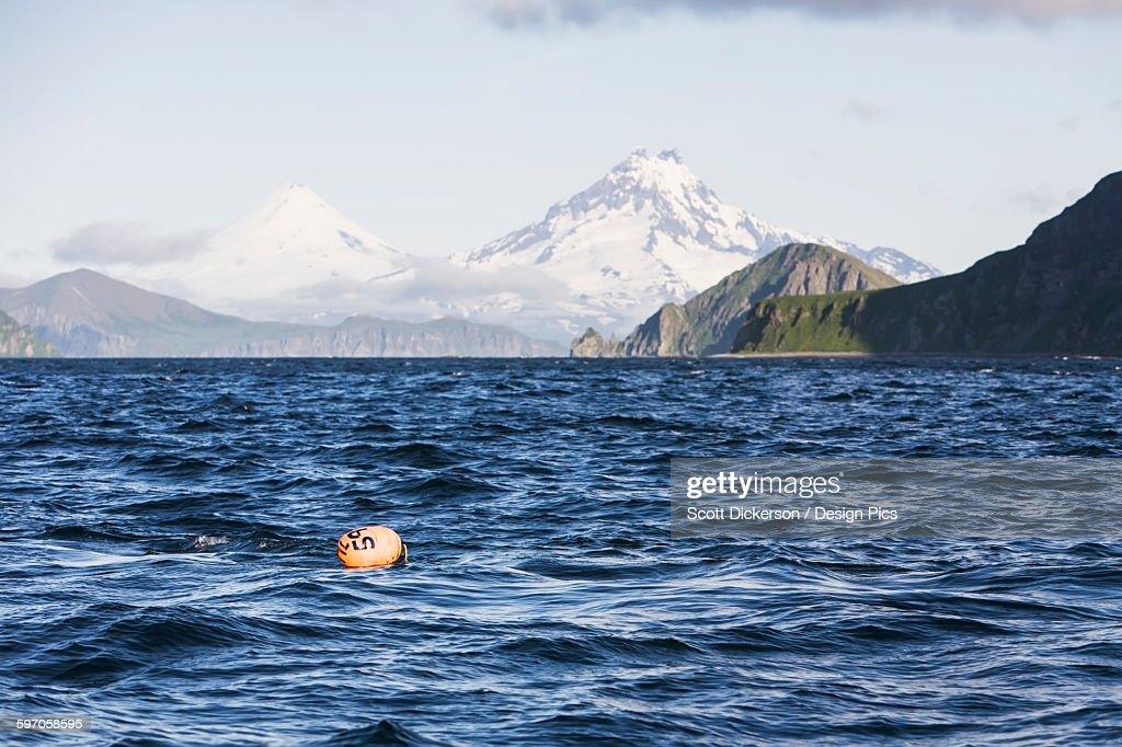 Shishaldin Volcano And Isanotski Peaks In The Background Of The Rugged Cliff Shoreline Of Cape Pankof On Unimak Island, Eastern Aleutian Islands : Stock Photo