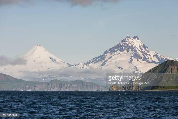 Shishaldin Volcano And Isanotski Peaks In The Background Of The Rugged Cliff Shoreline Of Cape Pankof On Unimak Island, Eastern Aleutian Islands