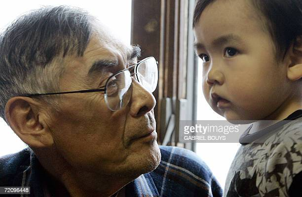 Johnny Weyiouamma Sr looks at his grandson Keith 26 September 2006 in Shishmaref Alaska The village home of Inupiat Eskimos is located 20 miles south...