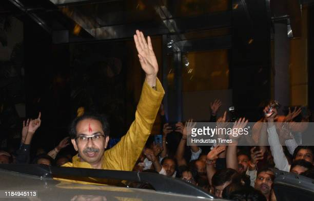 Shiv Sena Chief Udhhav Thackeray waves at supporters as he leaves after attending the joint meeting of Shiv Sena NCP and Congress party at Trident...