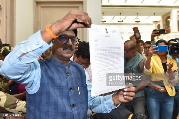 Shiv Sena Member of Parliament Arvind Sawant holds up his resignation letter from the cabinet during a press conference at Maharashtra Sadan on...