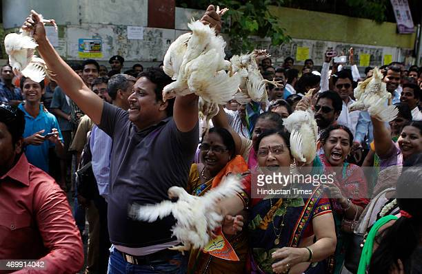 Shiv Sena workers holding and waving live chicken in the air as part of celebrations to mark their parties victory in the Bandra bypolls on April 15...