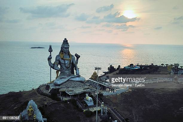 shiva statue by sea against sky during sunset - shiva stock pictures, royalty-free photos & images