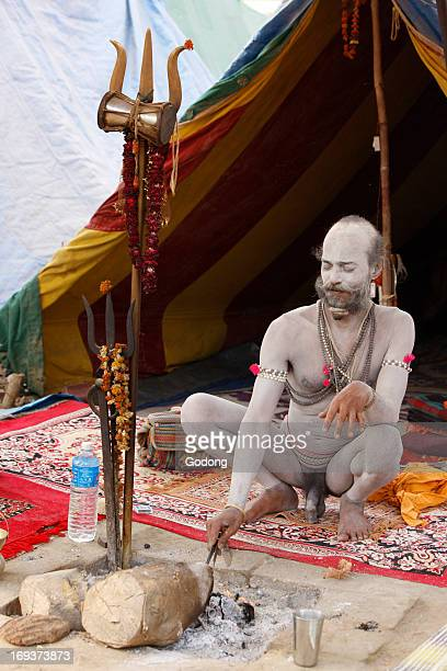 Shivaite Naga sadhu poking a sacred fire in his akhara at the Kumbh Mela in Hardwar