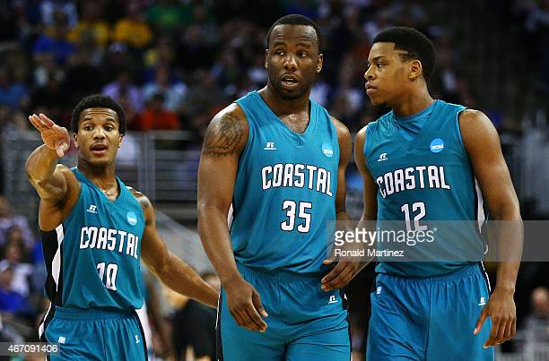 Shivaughn Wiggins Marcus Freeman and Michel Enanga of the Coastal Carolina Chanticleers talk in the first half against the Wisconsin Badgers during...