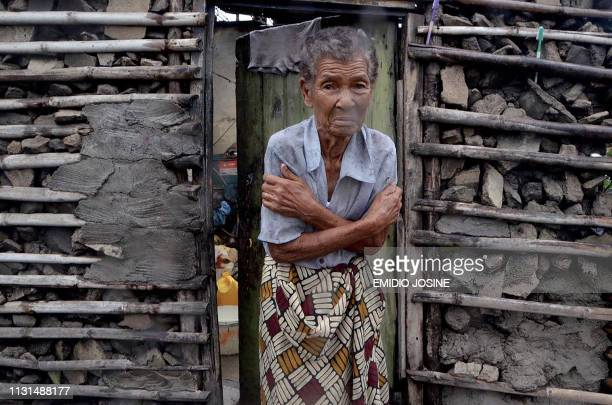 TOPSHOT A shivering displaced woman is portrayed in the doorframe of a house in Beira on March 19 2019 More than a thousand people are feared to have...