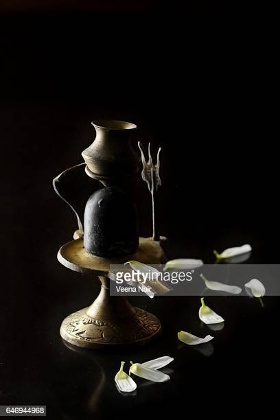 shivling/lord shiva idol with flowers against black background - maha shivaratri stock photos and pictures