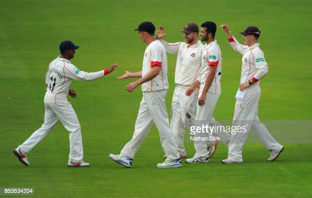 Shivnarine Chanderpaul of Lancashire high fives his team mates after catching Rory Burns of Surrey during the County Championship Division One match...