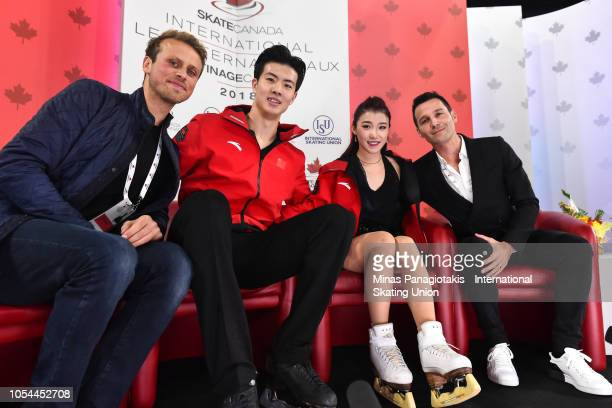 Shiyue Wang and Xinyu Liu of China pose with their coaching staff on day two during the ISU Grand Prix of Figure Skating Skate Canada International...