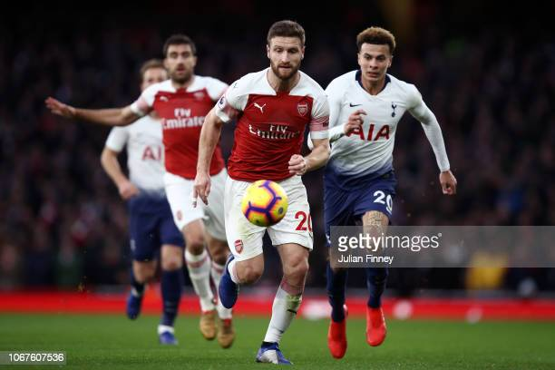 Shkodran Mustafi of Arsenal and Dele Alli of Tottenham Hotspur chase down the ball during the Premier League match between Arsenal FC and Tottenham...