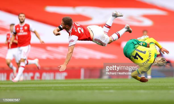 Shkodran Mustafi of Arsenal and Todd Cantwell of Norwich City collide as they compete for a header during the Premier League match between Arsenal FC...