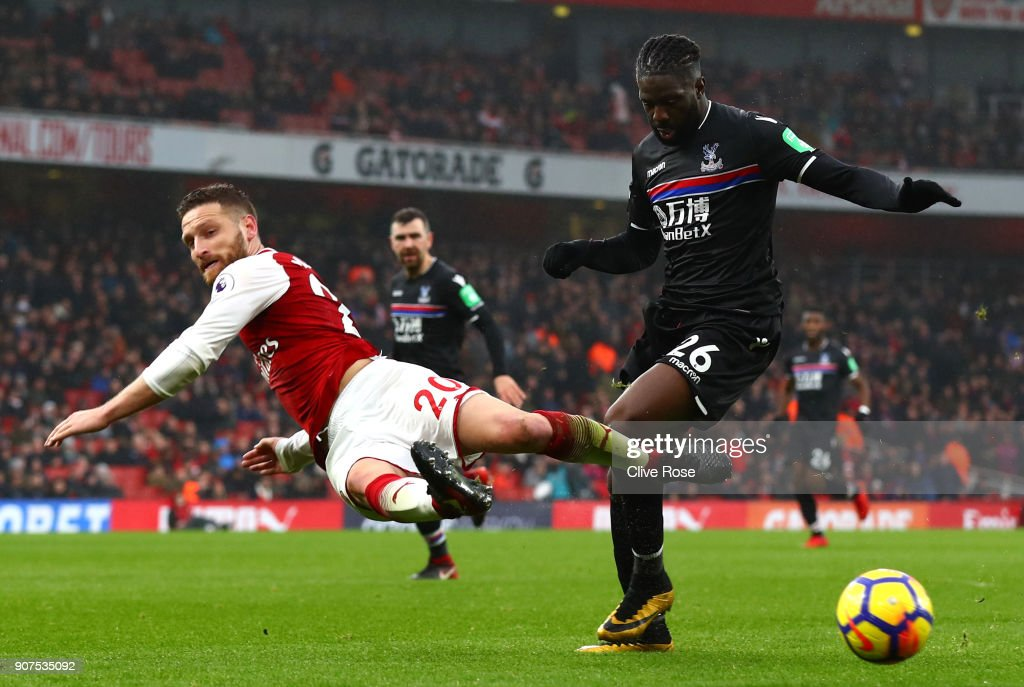 Shkodran Mustafi of Arsenal attempts to tackle Bakary Sako of Crystal Palace during the Premier League match between Arsenal and Crystal Palace at Emirates Stadium on January 20, 2018 in London, England.