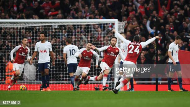 Shkodran Mustafi of Arsenal celebrates with team mates after scoring his sides first goal during the Premier League match between Arsenal and...