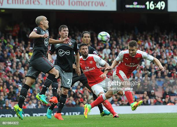 Shkodran Mustafi of Arsenal challenged by Oriol Romeu and Jose Fonte of Southampton during the Premier League match between Arsenal and Southampton...