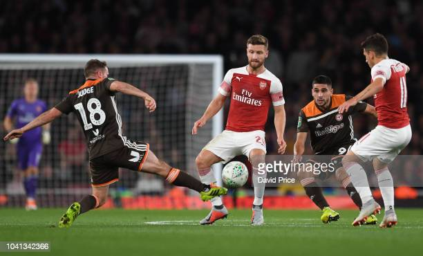 Shkodran Mustafi of Arsenal challenges Alan Judge of Brentford during the Carabao Cup Third Round match between Arsenal and Brentford at Emirates...