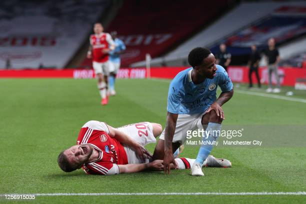 Shkodran Mustafi of Arsenal goes down injured as Raheem Sterling of Manchester City reacts during the FA Cup Semi Final match between Arsenal and...