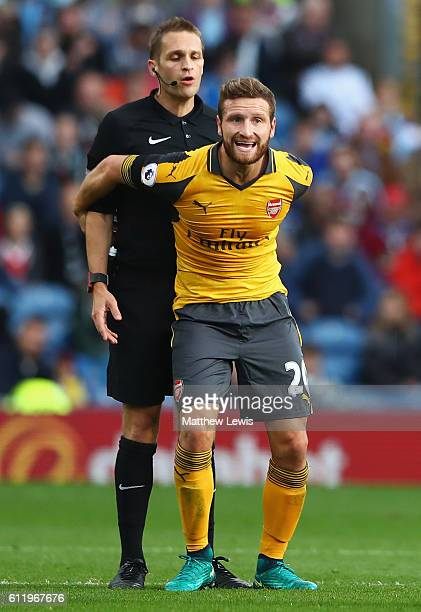 Shkodran Mustafi of Arsenal grabs refree Craig Pawson during the Premier League match between Burnley and Arsenal at Turf Moor on October 2 2016 in...