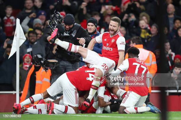 Shkodran Mustafi of Arsenal jumps on the pile of his teammates as they celebrate their 4th goal during the Premier League match between Arsenal FC...