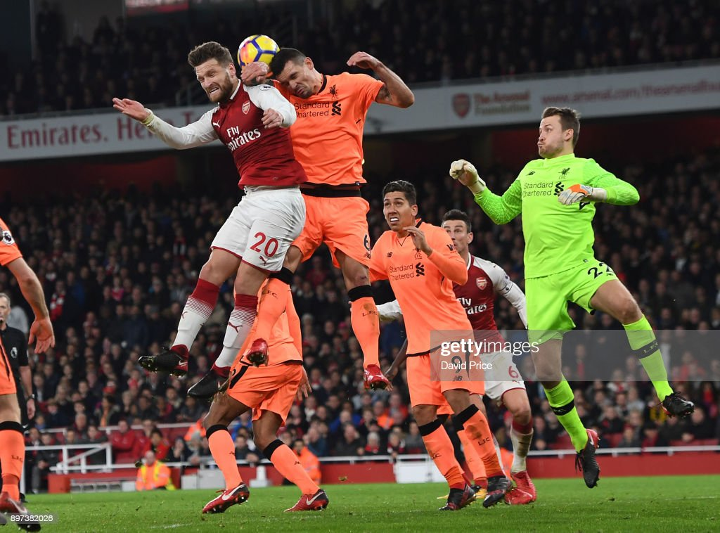 Shkodran Mustafi of Arsenal jumps with Dejan Lovren of Liverpool during the Premier League match between Arsenal and Liverpool at Emirates Stadium on December 22, 2017 in London, England.