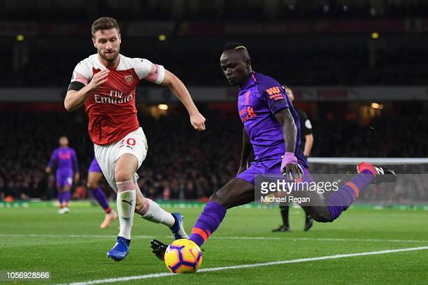 Shkodran Mustafi of Arsenal looks on as Sadio Mane of Liverpool shoots during the Premier League match between Arsenal FC and Liverpool FC at...