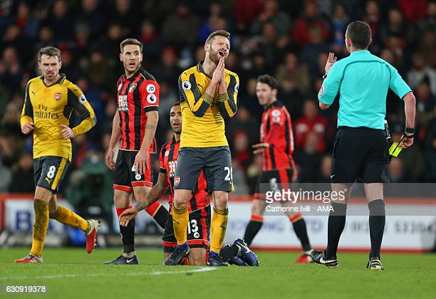 Shkodran Mustafi of Arsenal reacts as Referee Michael Oliver heads towards him with a yellow card during the Premier League match between AFC...