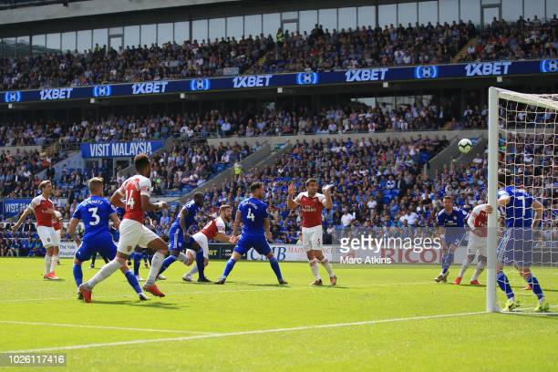 Shkodran Mustafi of Arsenal scores the opening goal during the Premier League match between Cardiff City and Arsenal FC at Cardiff City Stadium on...
