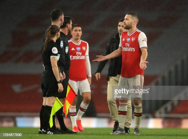 Shkodran Mustafi of Arsenal speaks with Match Referee Chris Kavanagh following the Premier League match between Arsenal FC and Leicester City at...