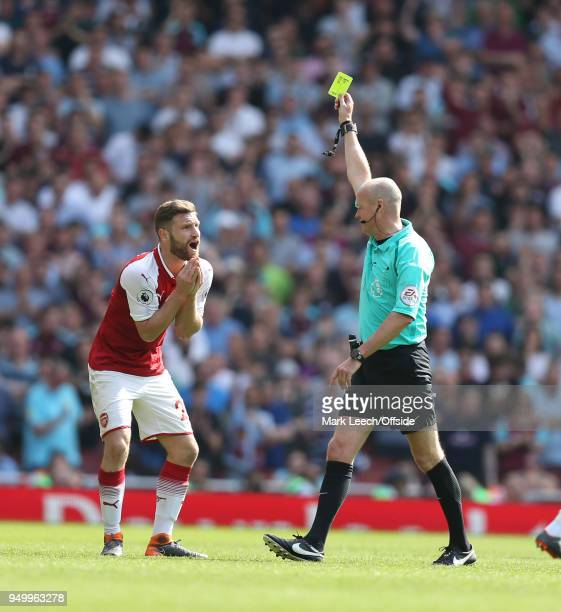Shkodran Mustafi of Arsenal watches in disbelief as he is shown the yellow card by referee Lee Mason during the Premier League match between Arsenal...
