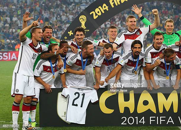 Shkodran Mustafi of Germany holds a jersey of the injured Marco Reus as he celebrates with teammates after defeating Argentina 10 in extra time...