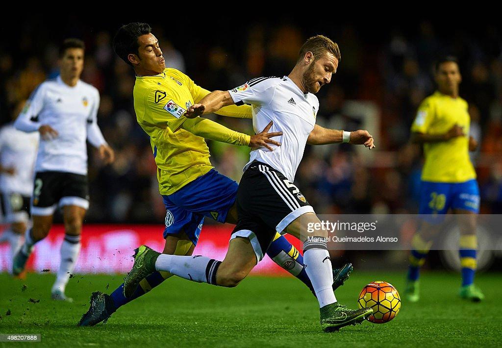 Shkodran Mustafi (5) of Valencia is tackled by Araujo of Las Palmas during the La Liga match between Valencia CF and UD Las Palmas at Estadi de Mestalla on November 21, 2015 in Valencia, Spain.