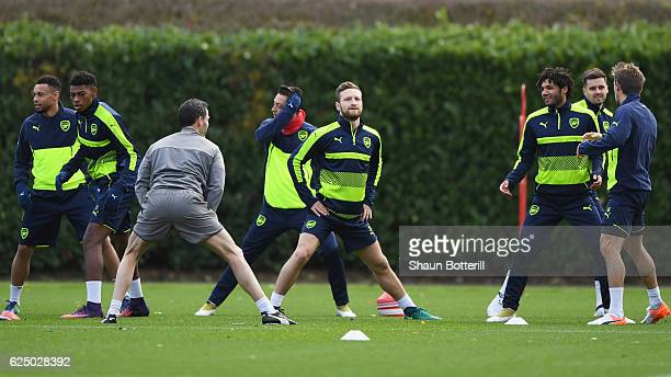 Shkodran Mustafi stretches with team mates during an Arsenal training session on the eve of their UEFA Champions League match against Paris...
