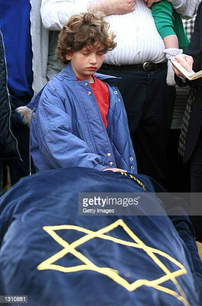 Shlomit Dudevsky aged 10 lays her hand on the shroudcovered body of her mother Hannah Dudevsky a 39yearold Jewish woman who was killed by Palestinian...