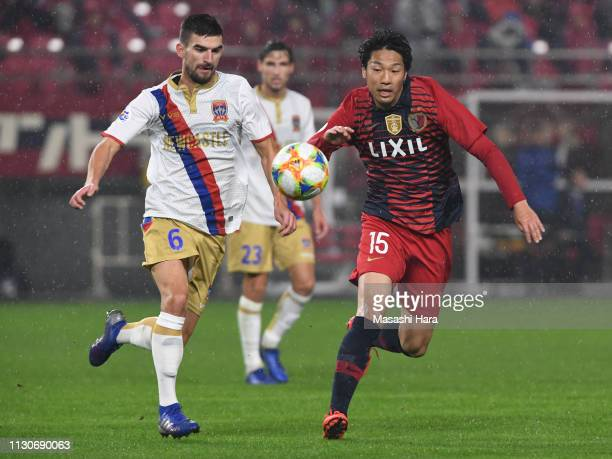 Sho Ito of Kashima Antlers and Steven Ugarkovic of Newcastle Jets compete for the ball during the AFC Champions League play off between Kashima...