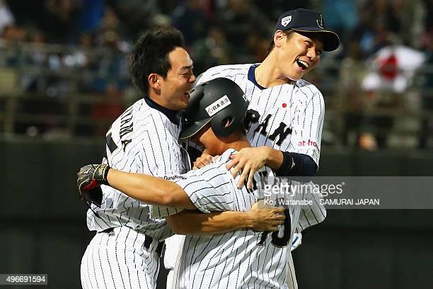 Sho Nakata of Japan is congratulated by his team mate Hayato Sakamoto and Shogo Akiyama after hitting the game winning single in the bottom of ninth...
