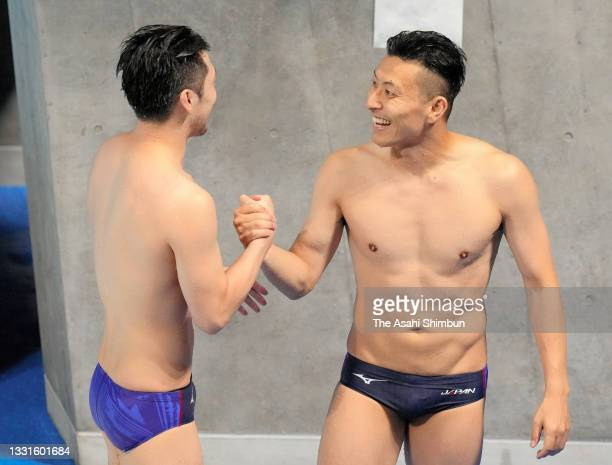 Sho Sakai and Ken Terauchi of Team Japan shake hands after competing in the Men's Synchronised 3m Springboard final on day five of the Tokyo 2020...