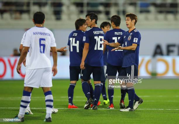 Sho Sasaki and Tsukasa Shiotani of Japan in discussion with Islom Tukhtakhodjaev of Uzbekistan after Japan's second goal during the AFC Asian Cup...