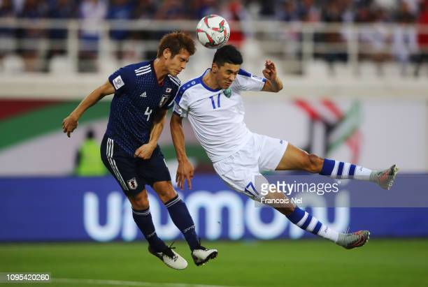 Sho Sasaki of Japan and Dostonbek Khamdamov of Uzbekistan jump for a header during the AFC Asian Cup Group F match between Japan and Uzbekistsn at...