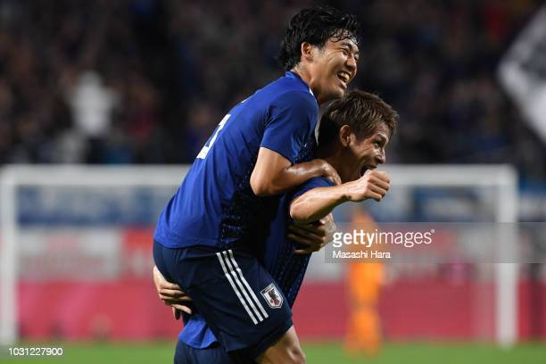 Sho Sasaki of Japan celebrates after scoring the opening goal with teammate Wataru Endo during the international friendly match between Japan and...