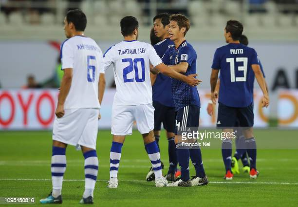 Sho Sasaki of Japan in discussion with Islom Tukhtakhodjaev of Uzbekistan after Japan's second goal during the AFC Asian Cup Group F match between...