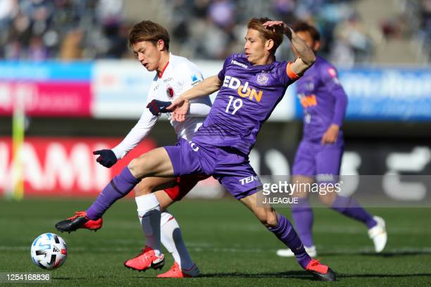 Sho Sasaki of Sanfrecce Hiroshima and Katsuya Nagato of Kashima Antlers compete for the ball during the J.League MEIJI YASUDA J1 match between...