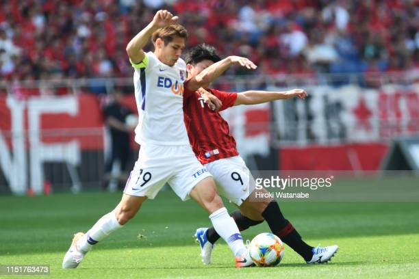 Sho Sasaki of Sanfrecce Hiroshima and Yuki Muto of Urawa Red Diamods compete for the ball during the J.League J1 match between Urawa Red Diamonds and...