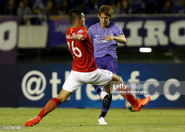 Sho Sasaki of Sanfrecce Hiroshima controls the ball under pressure of Guangzhou Evergrande's midfielder Huang Bowen during the AFC Champions League...
