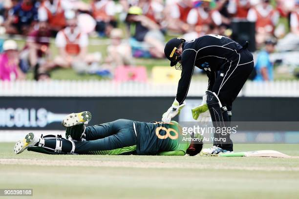 Shoaib Malik of Pakistan gets hit on the head by a ball as Tom Latham of New Zealand rushes to him during game four of the One Day International...