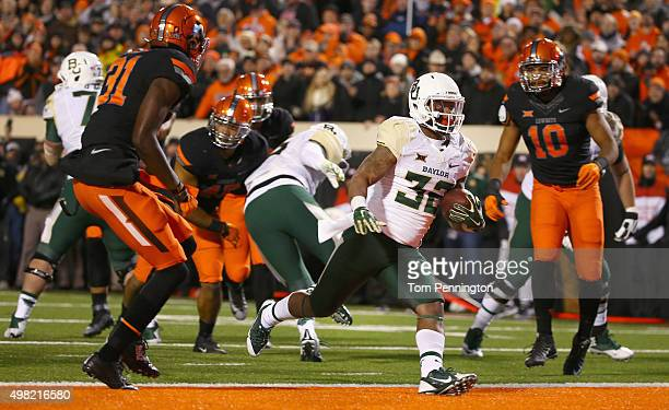 Shock Linwood of the Baylor Bears scores a touchdown against Tre Flowers of the Oklahoma State Cowboys and Seth Jacobs of the Oklahoma State Cowboys...
