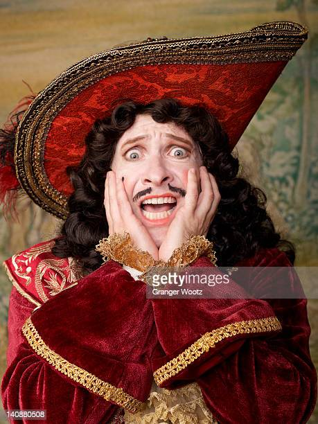 Shocked actor dressed in old-fashioned costume on stage