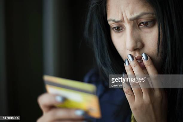 驚いたと不安若い女性を見ているクレジットカードが必要です。
