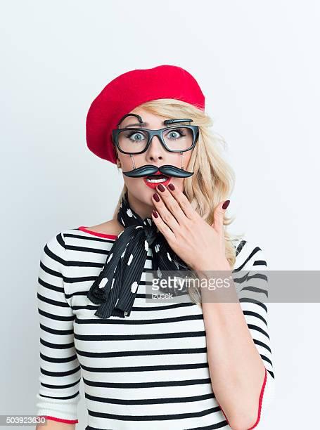 Chocado loura Fr mulher vestindo boné vermelho e máscara facial
