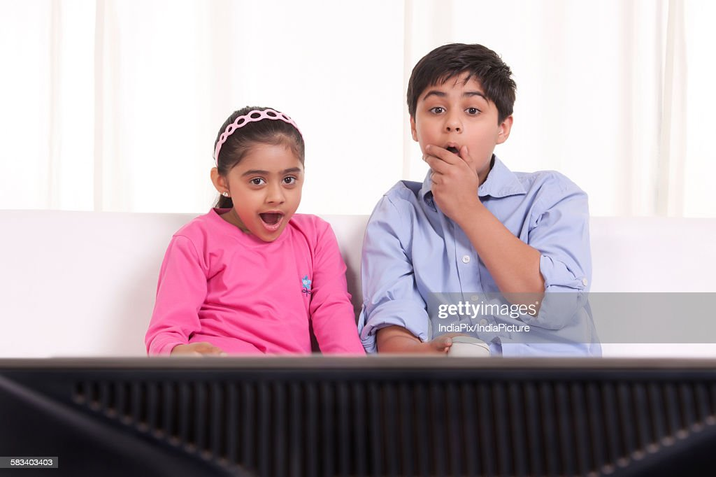 Shocked brother and sister watching tv : Stock Photo