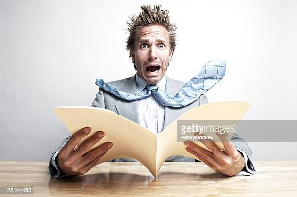 Shocked Businessman Office Worker Opening File Folder at Desk